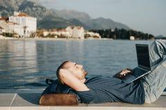 Hombre joven hermoso que se relaja y que trabaja en el ordenador portátil cerca Imagenes de archivo