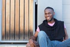 Hombre joven hermoso que se sienta al aire libre con baloncesto Foto de archivo libre de regalías