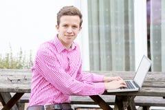 Hombre joven hermoso que se sienta al aire libre con su ordenador portátil Fotos de archivo libres de regalías