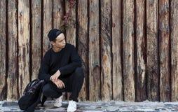 Hombre joven hermoso que se sienta cerca de una pared de madera Fotografía de archivo