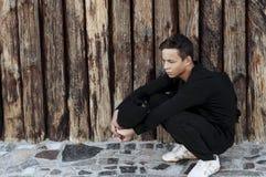 Hombre joven hermoso que se sienta cerca de una pared de madera Foto de archivo