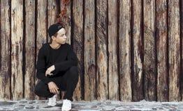 Hombre joven hermoso que se sienta cerca de una pared de madera Fotos de archivo libres de regalías