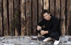 Hombre joven hermoso que se sienta cerca de una pared de madera Imagenes de archivo