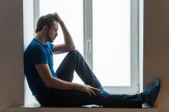 Hombre joven hermoso que se sienta en alféizar Fotografía de archivo