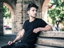 Hombre joven hermoso que se sienta en calle europea de la ciudad fotos de archivo libres de regalías