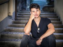 Hombre joven hermoso que se sienta en callejón europeo de la ciudad imagenes de archivo
