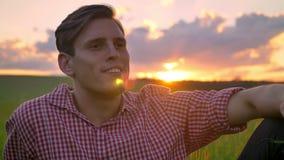 Hombre joven hermoso que se sienta en campo de trigo y que mastica la paja, mirando adelante, hermosa vista con puesta del sol en metrajes