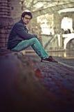 Hombre joven hermoso que se sienta en el centro de ciudad imagen de archivo
