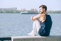 Hombre joven hermoso que se sienta en el muelle del río Fotografía de archivo libre de regalías