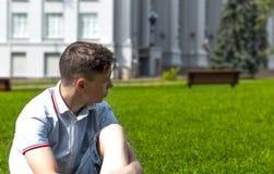 Hombre joven hermoso que se sienta en hierba cerca del edificio gris Imágenes de archivo libres de regalías