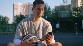 Hombre joven hermoso que se sienta en la cancha de básquet y que mecanografía en el teléfono, mirando la cámara, sosteniendo la b almacen de metraje de vídeo