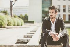 Hombre joven hermoso que se sienta en la ciudad Imagen de archivo libre de regalías