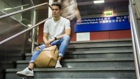Hombre joven hermoso que se sienta en las escaleras imagen de archivo