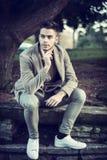 Hombre joven hermoso que se sienta en parque de la ciudad Fotos de archivo