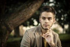 Hombre joven hermoso que se sienta en parque de la ciudad Imagen de archivo