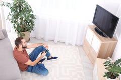 Hombre joven hermoso que se sienta en piso y la TV de observación imagen de archivo