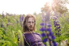 Hombre joven hermoso que se sienta en un campo de flor Foto de archivo