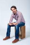 Hombre joven hermoso que se sienta en una caja de madera imágenes de archivo libres de regalías