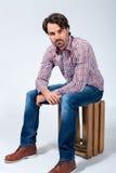 Hombre joven hermoso que se sienta en una caja de madera foto de archivo libre de regalías