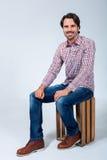 Hombre joven hermoso que se sienta en una caja de madera imagen de archivo libre de regalías