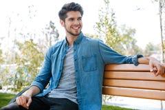 Hombre joven hermoso que se sienta en una sonrisa del banco Foto de archivo libre de regalías