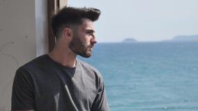 Hombre joven hermoso que se sienta por la ventana imagen de archivo