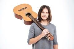 Hombre joven hermoso que sostiene la guitarra en su hombro Imagen de archivo