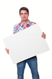 Hombre joven hermoso que sostiene la tarjeta blanca en blanco Fotografía de archivo libre de regalías