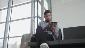 Hombre joven hermoso que sostiene Tablet PC y que trabaja en el aeropuerto, tecnología, concepto que viaja almacen de metraje de vídeo