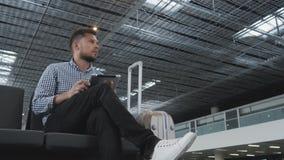 Hombre joven hermoso que sostiene Tablet PC y que trabaja en el aeropuerto, tecnología, concepto que viaja almacen de video