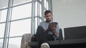 Hombre joven hermoso que sostiene Tablet PC y que trabaja en el aeropuerto, tecnología, concepto que viaja imagen de archivo