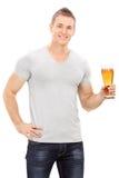 Hombre joven hermoso que sostiene una pinta de cerveza imagen de archivo libre de regalías