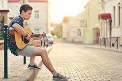 Hombre joven hermoso que toca la guitarra Imagen de archivo libre de regalías