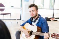 Hombre joven hermoso que toca la guitarra acústica Foto de archivo libre de regalías