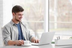 Hombre joven hermoso que trabaja en la computadora portátil imágenes de archivo libres de regalías
