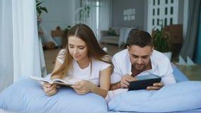 Hombre joven hermoso que usa las fotos de la demostración de tableta en la tableta a su libro de lectura del girfriend y mintiend Fotografía de archivo