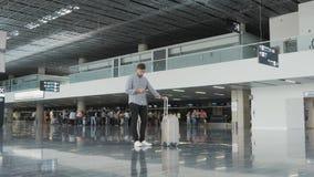 Hombre joven hermoso que usa Smartphone y trabajando en el aeropuerto mientras que espera su cola el registro, viajando metrajes