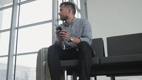 Hombre joven hermoso que usa Smartphone y trabajando en el aeropuerto mientras que espera su cola el registro, viajando almacen de metraje de vídeo