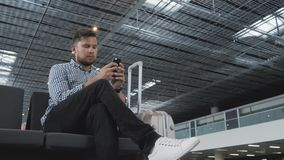 Hombre joven hermoso que usa Smartphone y trabajando en el aeropuerto mientras que espera su cola el registro, viajando almacen de video