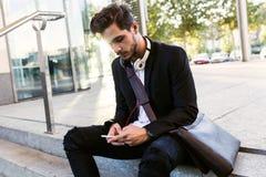 Hombre joven hermoso que usa su teléfono móvil en la calle Fotos de archivo libres de regalías