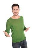 Hombre joven hermoso satisfecho aislado con las manos abiertas en blanco. Imagenes de archivo