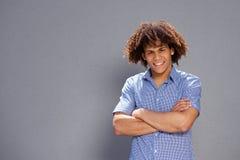 Hombre joven hermoso sonriente contra fondo gris foto de archivo