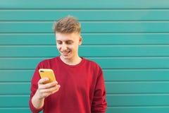 Hombre joven hermoso usando un smartphone, mirando la pantalla y sonriendo en el fondo de una pared de la turquesa fotos de archivo libres de regalías