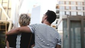 Hombre joven hermoso y mujer que caminan a lo largo de la calle del verano de New York City junto, charlando, abrazando y disfrut almacen de metraje de vídeo