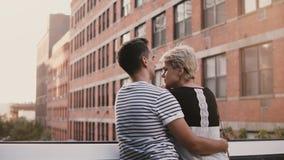 Hombre joven hermoso y mujer que se colocan y que abrazan en un puente que habla, gozando de paisaje urbano asombroso y de edific almacen de video