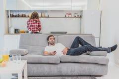 Hombre joven hilarante hermoso que sostiene un teledirigido Durante esto, la TV está mirando mientras que se sienta en el sofá en imagen de archivo