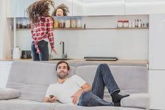Hombre joven hilarante hermoso que sostiene un teledirigido Durante esto, la TV está mirando mientras que se sienta en el sofá en foto de archivo libre de regalías