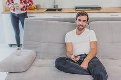 Hombre joven hilarante hermoso que sostiene un teledirigido Durante esto, la TV está mirando mientras que se sienta en el sofá en foto de archivo