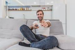 Hombre joven hilarante hermoso que sostiene un teledirigido Durante esto, la TV está mirando mientras que se sienta en el sofá en fotos de archivo libres de regalías