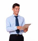 Hombre joven hispánico en lazo usando la PC de la tableta Fotos de archivo
